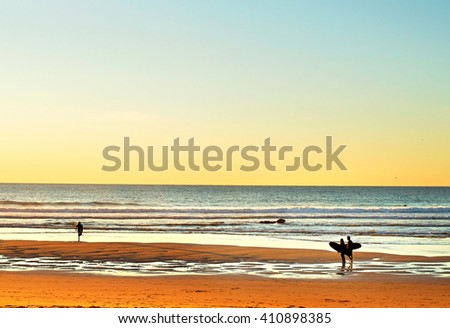 Couple surfers at surfing spot on the ocean beach at sunset - stock photo