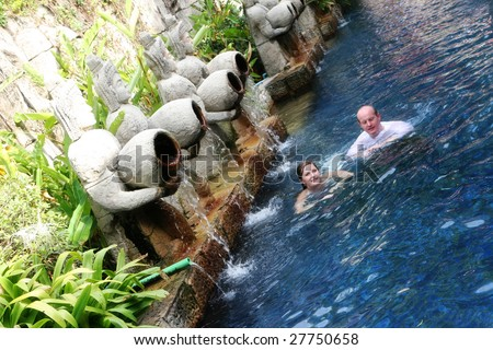 Couple swimming under Thai statues overlooking a swimming pool area - travel and tourism.