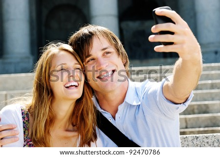 couple take a picture together while visiting a tourist attraction, smiling and having fun - stock photo