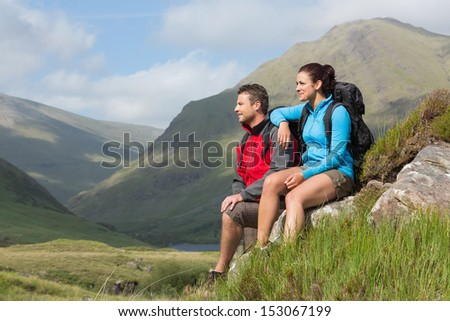 Couple taking a break after hiking uphill in the countryside - stock photo