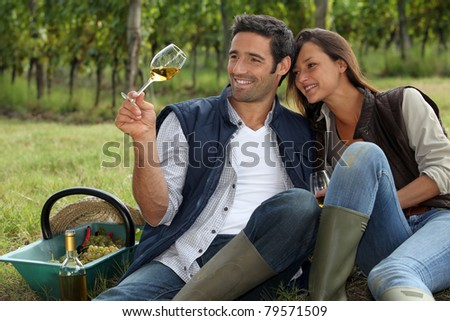 Couple taking a break from picking grapes - stock photo