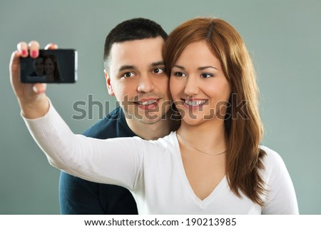 Couple taking a photo of thmeselves with a smart phone. - stock photo