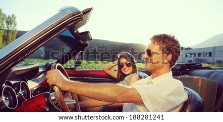 Couple taking a road trip in vintage convertible - stock photo