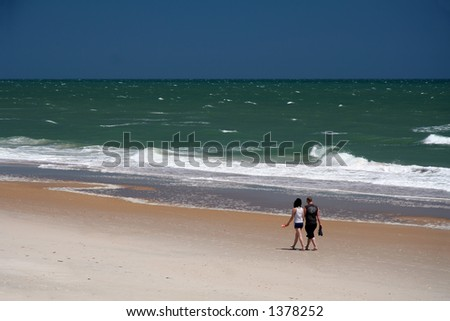 Couple taking a romantic stroll on the beach - stock photo