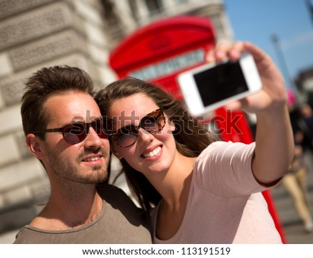 Couple taking a self portrait in the streets of London - stock photo
