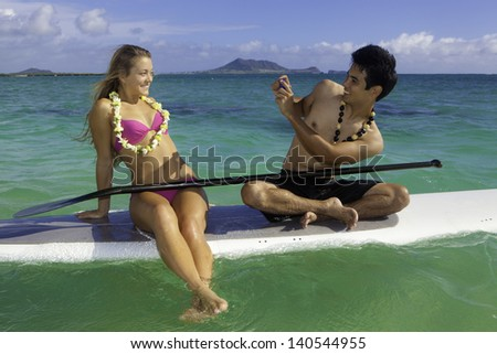 couple taking pictures with cell phone on a paddle board in the ocean - stock photo