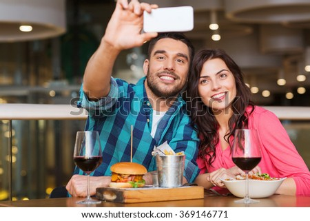 couple taking selfie by smartphone at restaurant - stock photo