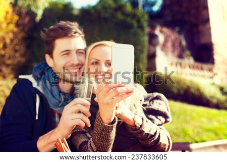 Couple taking Selfie in autumn while drinking a cocktail - stock photo