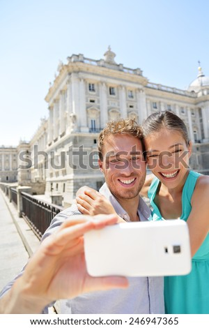 Couple taking selfie photo on smartphone in Madrid. Romantic man and woman in love using smart phone to take self-portrait photograph on travel in Madrid, Spain.