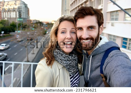 couple taking selfie photograph in city on vacation - stock photo