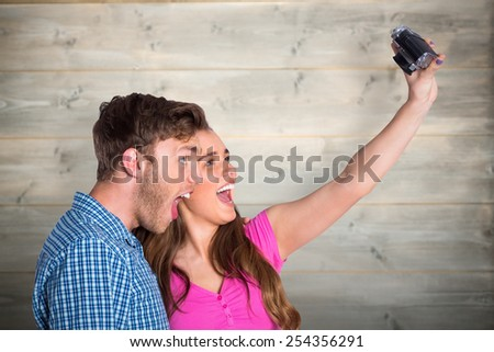 Couple taking selfie with digital camera against bleached wooden planks background - stock photo