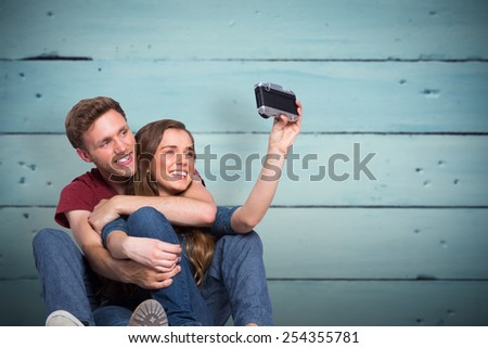 Couple taking selfie with digital camera against painted blue wooden planks - stock photo
