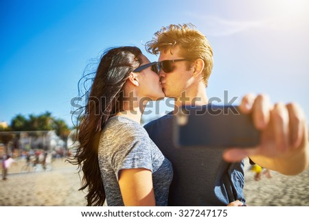 couple taking selfie with smart phone during kiss with lens flare and shot with selective focus - stock photo