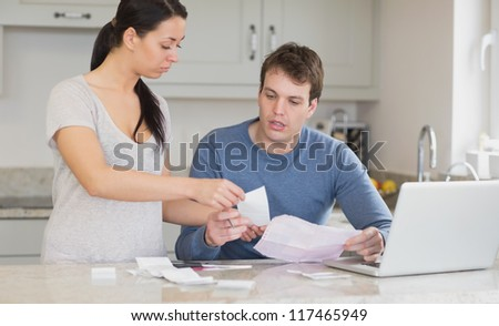 Couple talking about bills with laptop in kitchen - stock photo