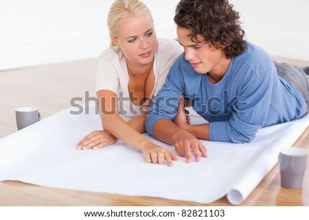 Couple talking about their future room with a plan while lying on the floor