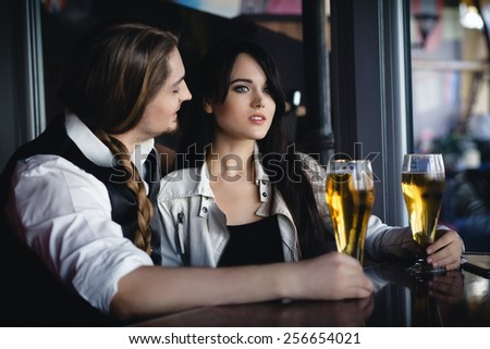 couple talking in a bar with beer