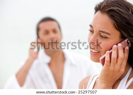 Couple talking on the phone and smiling outdoors