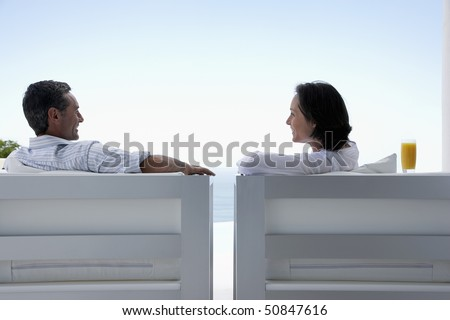 Couple talking, sitting on lounge chairs, outdoors - stock photo
