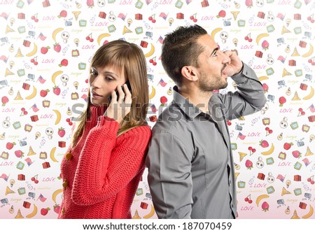 Couple talking to mobile over cute background with icons - stock photo