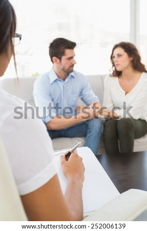Couple talking with their psychologist in the office - stock photo