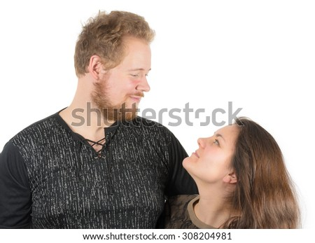 couple: tall man and short woman smiling and looking at each other - stock photo