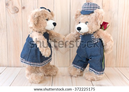 couple teddy bears with rose on wood background, love concept - stock photo