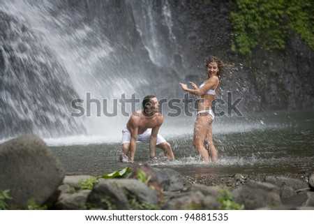 Couple throwing water at each other under waterfalls. - stock photo