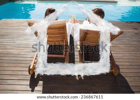 Couple toasting champagne by swimming pool against house outline in clouds - stock photo