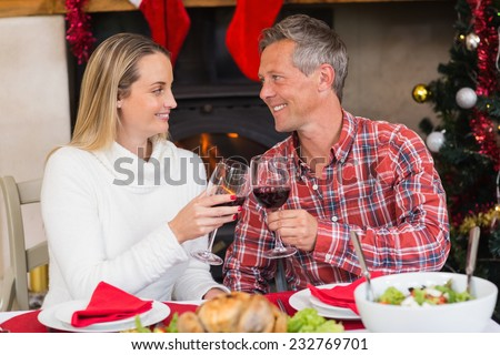 Couple toasting each other with red wine at home in the living room
