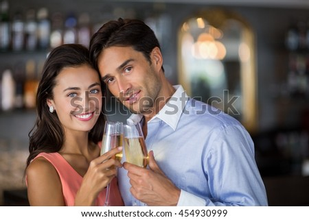 Couple toasting glasses of wine in restaurant