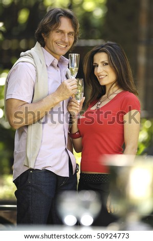 Couple toasting in the garden - stock photo