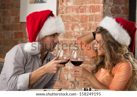 Couple toasting wine glasses at restaurant while celebrating Christmas - stock photo