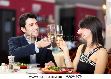 Couple toasting wine in a restaurant - stock photo