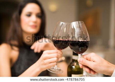 Couple toasting wineglasses in a luxury restaurant. Focus on the glass