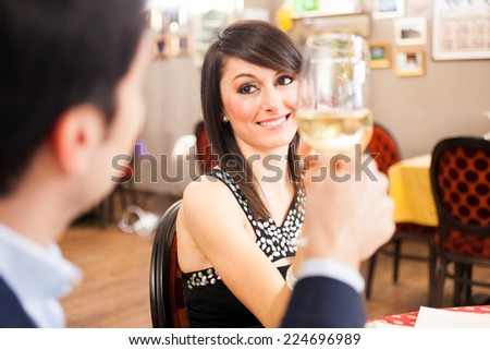 Couple toasting wineglasses in a restaurant - stock photo
