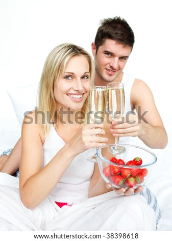 Couple toasting with champagne and strawberries to an engagement  in bed