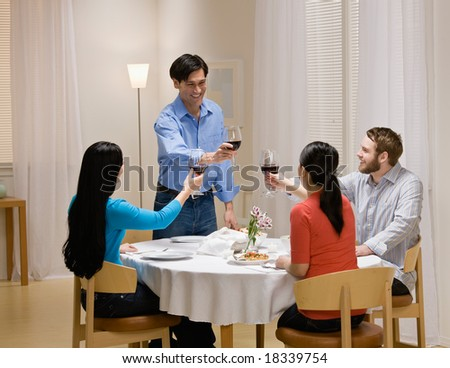 Couple toasting with red wine at elegant dinner party - stock photo