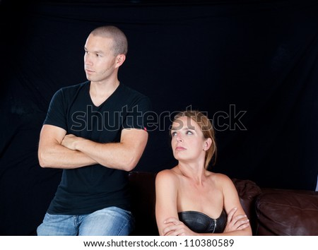 Couple together and angry at each other, he has his arms crossed and she glares at him and he looks away