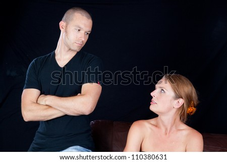 Couple together and angry at each other, he has his arms crossed and they are glaring at each other - stock photo