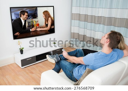 Couple Together Sitting On Sofa Watching Movie On Television
