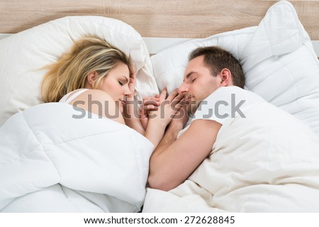 Couple Together Sleeping In Bed At Home - stock photo
