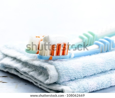 Couple toothbrushes  with toothpaste on a towel