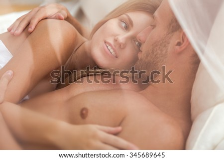 Couple totally in love lying in bed - stock photo
