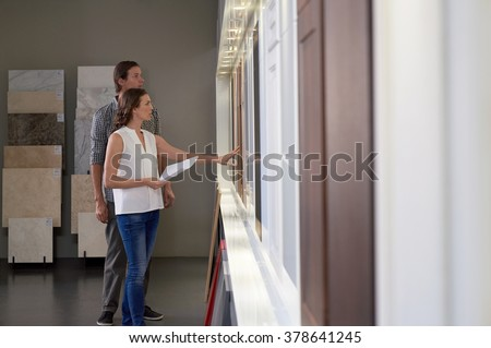 Couple touching different finishes in modern kitchen shop showroom while planning their dream kitchen - stock photo