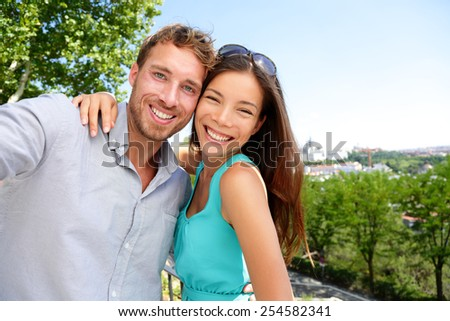Couple tourists taking travel selfie self-portrait in Madrid park, Spain in summer. Young adults mixed race asian caucasian smiling at smartphone camera for a snapshot during their holidays in Europe. - stock photo