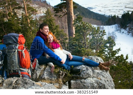 couple tourists woman and man sitting at the camp in the forest and mountains - stock photo