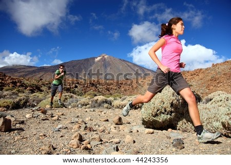 Couple trail running in spectacular volcano landscape on Teide, Tenerife. - stock photo