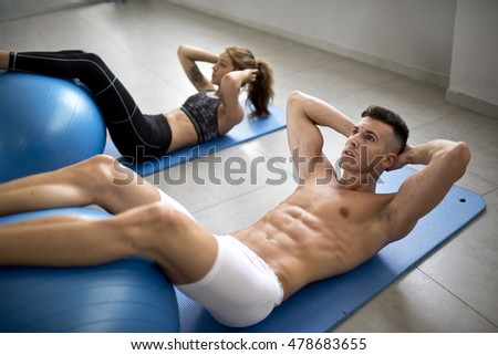 couple training abdominal muscle in gym room