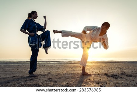 couple training in martial arts on the beach at sunrise. karate kick versus wu shu parry. concept about martial arts - stock photo
