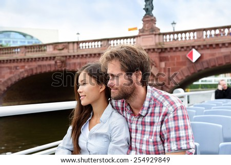 Couple travel in Berlin sightseeing on boat tour. Beautiful young multiracial adults relaxing on a cruise visiting the city on a day boating excursion for tourists. - stock photo